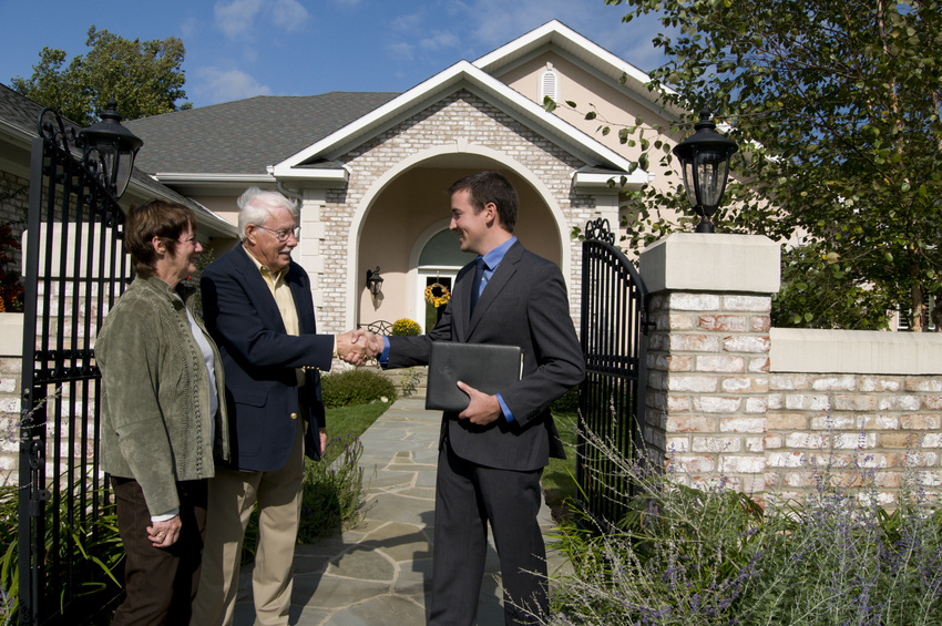 Real estate agents shaking hands with couple after purchasing homes for sale in Spring Branch, TX